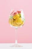 Macarrones multicolores en copa de vino en un fondo blanco y rosado Autor que procesa, foco selectivo, efecto de la película Imagen de archivo