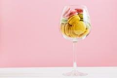 Macarrones multicolores en copa de vino en un fondo blanco y rosado El author& x27; s que procesa, espacio para el texto Imagen de archivo libre de regalías