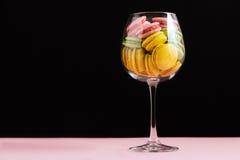Macarrones multicolores en copa de vino en un fondo negro y rosado Autor que procesa, foco selectivo, efecto de la película Fotos de archivo