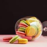 Macarrones multicolores en copa de vino en un fondo negro y rosado El autor que procesa, foco selectivo Imagenes de archivo