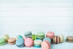 Macarrones o macaron deliciosos en un fondo de madera blanco, galletas de almendra en una tabla, espacio de la copia Foto de archivo