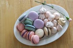 Macarrones o macaron franceses dulces y coloridos en blanco de cerámica Fotos de archivo