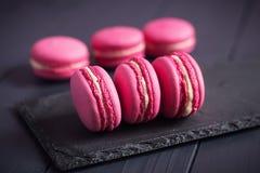Macarrones rosados de la frambuesa en fondo negro Fotos de archivo libres de regalías