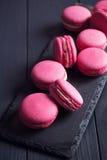 Macarrones rosados de la frambuesa en fondo negro Fotografía de archivo