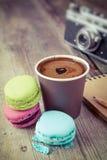 Macarrones, taza de café del café express, libro del bosquejo y cámara retra encendido Foto de archivo libre de regalías