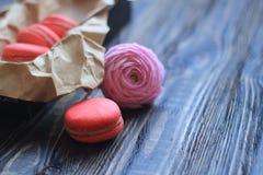 Macarrones y flores coloridos en la tabla Fotografía de archivo libre de regalías