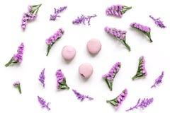Macarrones y flores para el desayuno ligero en el modelo blanco de la opinión superior del fondo del escritorio Fotos de archivo libres de regalías