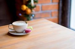 Macarrones y taza de café coloridos en fondo de la ventana imagenes de archivo