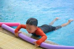 Macarronete da espuma da posse da criança ou do menino na barra lateral da piscina para flutuar d imagens de stock