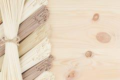 Macarronetes asiáticos crus das polias na placa de madeira bege macia com espaço da cópia, vista superior fotos de stock royalty free