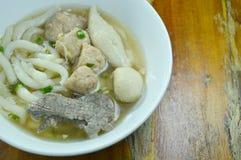 Macarronetes chineses da farinha de arroz que cobrem a carne de porco e o fígado triturados com a bola de peixes na sopa na bacia foto de stock