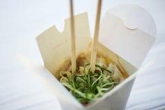 Macarronetes com carne de porco e vegetais na caixa para viagem na tabela de madeira fotografia de stock