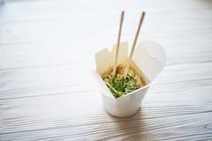 Macarronetes com carne de porco e vegetais na caixa para viagem na tabela de madeira foto de stock
