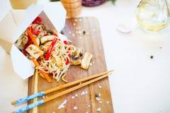 Macarronetes com cogumelo e vegetais na caixa para viagem na tabela de madeira fotografia de stock