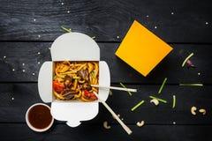 Macarronetes da fritada da agitação do Udon com carne e vegetais em uma caixa no fundo preto Com hashis e molho Foto de Stock Royalty Free