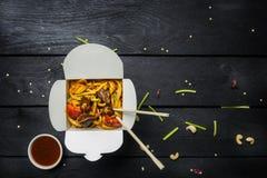 Macarronetes da fritada da agitação do Udon com carne e vegetais em uma caixa no fundo preto Com hashis e molho Imagem de Stock Royalty Free