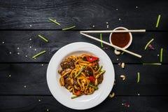 Macarronetes da fritada da agitação do Udon com carne e vegetais em uma placa branca no fundo de madeira preto Com hashis e molho Imagens de Stock