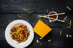 Macarronetes da fritada da agitação do Udon com carne e vegetais em uma placa branca no fundo preto Com hashis e caixa para macar Imagens de Stock Royalty Free