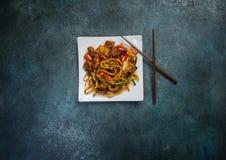 Macarronetes da fritada da agitação do Udon com carne ou pato e vegetais em uma placa branca quadrada Com chopsticks Vista superi Fotografia de Stock