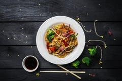 Macarronetes da fritada da agitação do Udon com galinha e vegetais em uma placa branca no fundo de madeira preto Com hashis e mol Imagem de Stock