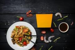 Macarronetes da fritada da agitação do Udon com marisco em uma placa branca no fundo preto Com hashis e caixa para macarronetes Imagem de Stock