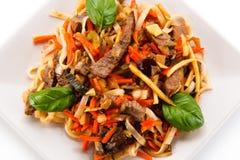 Macarronetes de arroz com carne, molho e vegetais Imagem de Stock