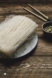 Macarronetes de arroz crus, na tabela de madeira rústica imagens de stock