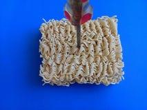 Macarronetes de Ramen ao lado da chave de fenda - conceito para fixar qualquer coisa que usa macarronetes - fundo azul foto de stock royalty free