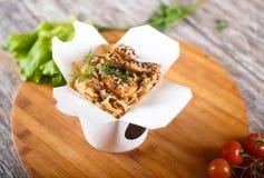 Macarronetes do frigideira chinesa com a galinha no empacotamento de papel imagem de stock