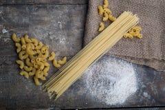 macarronetes e farinha na tabela Foto de Stock