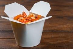 Macarronetes em uma caixa branca no fundo de madeira Foto de Stock Royalty Free