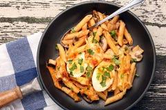 Macarronetes fritados com ovos e salsa no fundo de madeira Imagens de Stock
