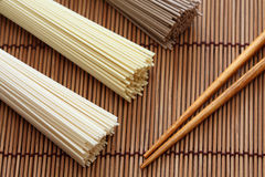 Macarronetes japoneses com os hashis no guardanapo de bambu Fotografia de Stock