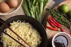 Macarronetes na bacia preta decorada na mesa de cozinha Imagens de Stock