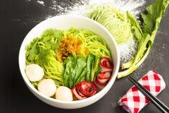Macarronetes no Vagabundo-Mee-MOO-Dang de Tailândia ou na massa de Ásia e macarronetes secados com o ingrediente na tabela preta  Fotografia de Stock