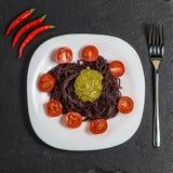 Macarronetes pretos com tomates e molho do pesto Fotografia de Stock Royalty Free