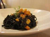 Macarronetes pretos italianos cozinhados com tinta do sepia do calamar, partes de calamar, molho de tomate e molho do pistache na imagens de stock royalty free