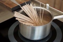 Macarronetes que estão sendo cozinhados no fogão da indução fotografia de stock royalty free