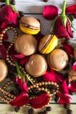 Macaruns mit roten Rosen und Kaffee Lizenzfreie Stockfotos