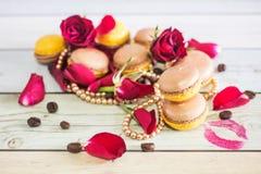 Macaruns mit roten Rosen und Kaffee Stockbilder