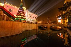 Christmas in Venetian Casino. Macau, China - December 8, 2016: Christmas tree illuminated in front of The Venetian Casino, reflecting in the lake at night. Cotai Stock Photos