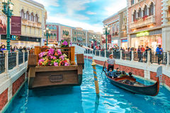 Macau - January 24, 2016: Gondolier rides tourists on a gondola along the mock canal of the Venetian Macau Resort Hotel which is t Stock Photos