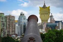 Old cannon opposite skyscrapers, Macau royalty free stock photos