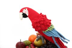 Macaw rojo y azul hecho a ganchillo en las falsas frutas Imagenes de archivo