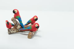 Macaws made in clay seated on a wood branch isolated in white ba Stock Photography