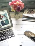 Macbook Air, Flower Bouquet and Magazines on White Table Royalty Free Stock Photos