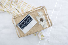 Macbook Beside Coffee Cup on Beige Woven Tray Stock Photos
