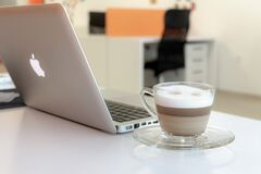 Macbook Pro Besides Clear Glass Mug Royalty Free Stock Photography