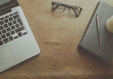 Macbook Pro Beside Black Framed Eyeglasses on Brown Wooden Surface Stock Image