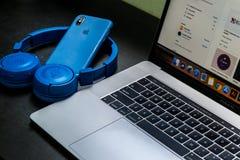 Macbook Pro Beside Blue Wireless Headphones stock photo